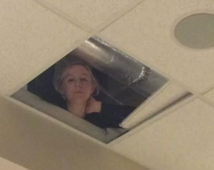 Woman looking down from the ceiling hole