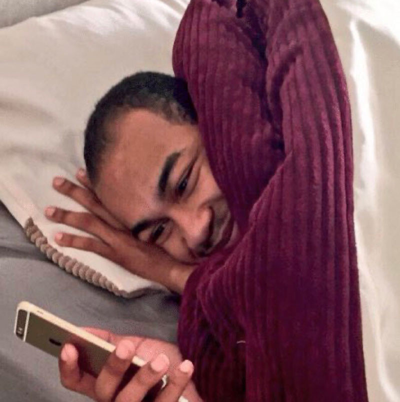 Man looking at phone smiling laying in bed with blanket meme